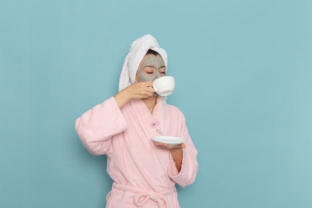 Вид спереди молодая женщина в розовом халате, пьющая кофе на синей стене, чистка красоты, крем для ухода за собой, душ