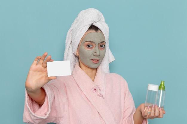 カードを保持しているピンクのバスローブと青い壁の美しさの水バスクリームセルフケアシャワーのスプレーで正面図若い女性