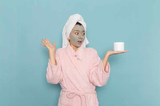 Вид спереди молодая женщина в розовом халате, держащая крем для лица на синей стене, чистка душа, крем для ухода за собой