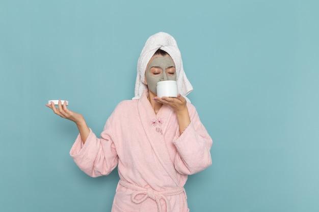 파란색 벽 아름다움 물 목욕 크림 셀프 케어 샤워에 크림을 들고 분홍색 목욕 가운에 전면보기 젊은 여성