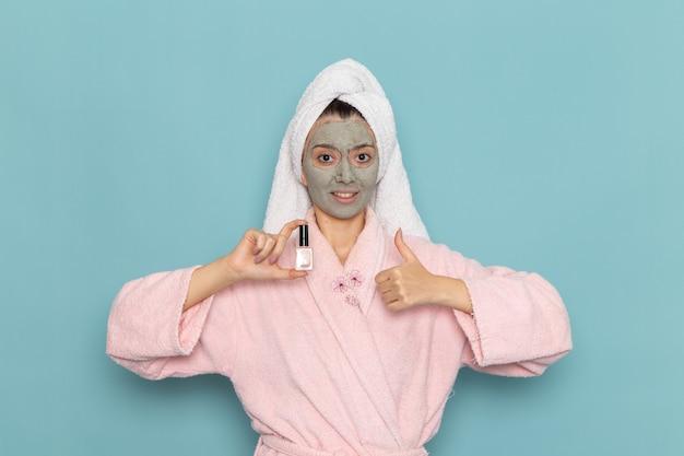 Вид спереди молодая женщина в розовом халате, держащая лак для ногтей на синей стене, чистящая красота, чистая вода, крем для ухода за собой, душ