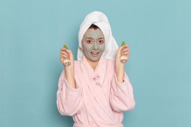 Вид спереди молодая женщина в розовом халате держит спреи на синей стене, очищая душ, крем для ухода за собой