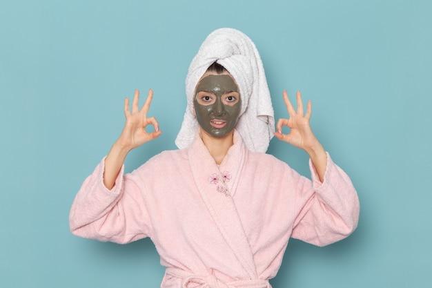 ピンクのバスローブを着た若い女性の正面図青い壁の美しさの水バスクリームセルフケアシャワーで彼女の顔にマスクを付けてポーズ