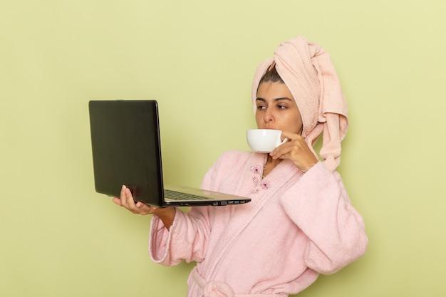 Вид спереди молодая женщина в розовом халате, использующая ноутбук и пьющая кофе на зеленой поверхности