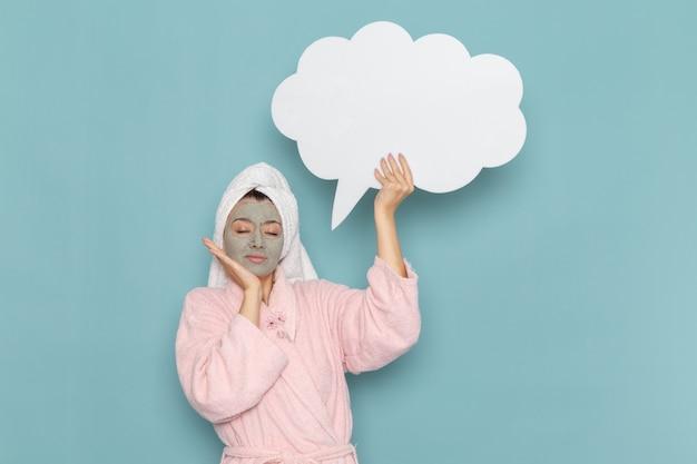 Вид спереди молодая женщина в розовом халате с маской на лице, держащая большой белый знак на синей стене, чистка душа, крем для ухода за собой