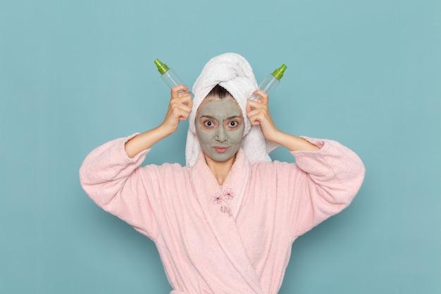 青い壁のシャワーのクリーニング美容セルフケアクリームにスプレーを保持している彼女の顔にマスクとピンクのバスローブを着た若い女性の正面図