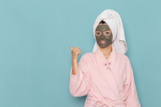 ピンクのバスローブを着た若い女性の正面図青い壁のシャワーのクリーニング美容セルフケアクリームの彼女の顔にマスク