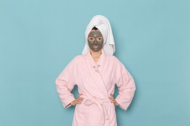正面図ピンクのバスローブを着た若い女性の顔にマスクを付けて青い壁のシャワーでポーズをとって美容セルフケアクリームを掃除