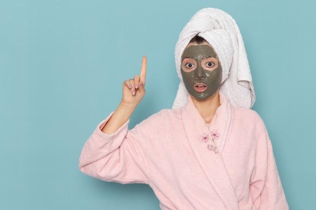 彼女の顔にマスクと青い壁のシャワークリーニング美容セルフケアクリームでポーズをとってピンクのバスローブを着た若い女性の正面図