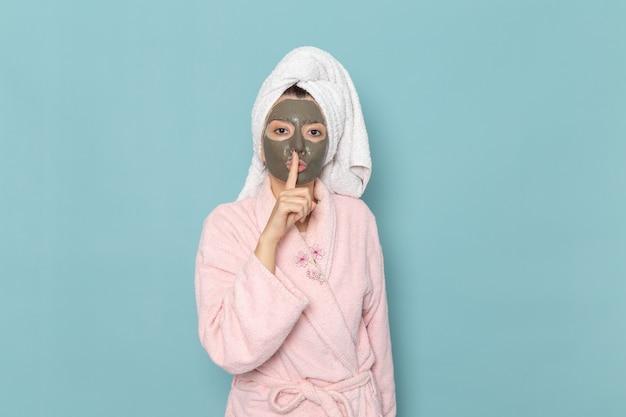 正面図ピンクのバスローブを着た若い女性の顔にマスクがあり、青い壁に沈黙のサインを示していますシャワークリーニング美容セルフケアクリーム