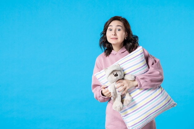 青い夜にピンクのパジャマを着た若い女性の正面図