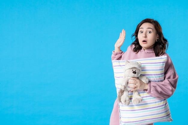 青い不眠症のベッドの夜の悪夢の夢のパーティーの休息で誰かと話しているピンクのパジャマを着た若い女性の正面図