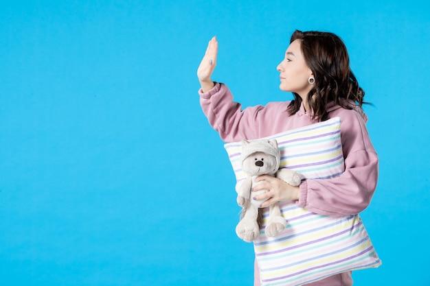 青いパーティーの不眠症のベッドの夜の夢の休息睡眠で誰かと話しているピンクのパジャマの正面図若い女性