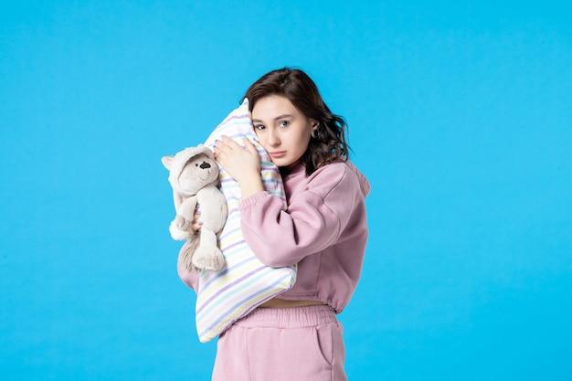 Вид спереди молодая женщина в розовой пижаме с маленьким игрушечным медведем и подушкой на синей кровати, ночной кошмар, сон, бессонница, вечеринка мечты