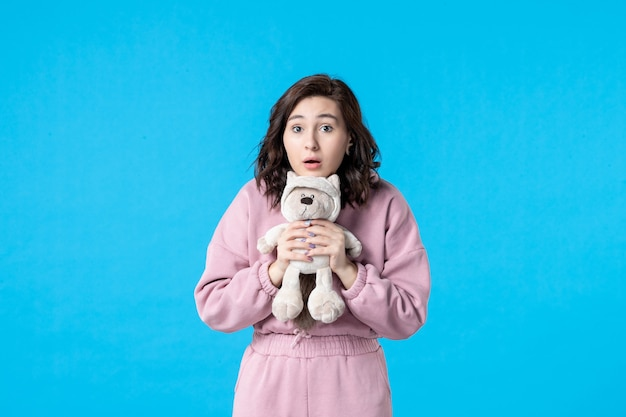 青に小さなおもちゃのクマとピンクのパジャマの正面図若い女性