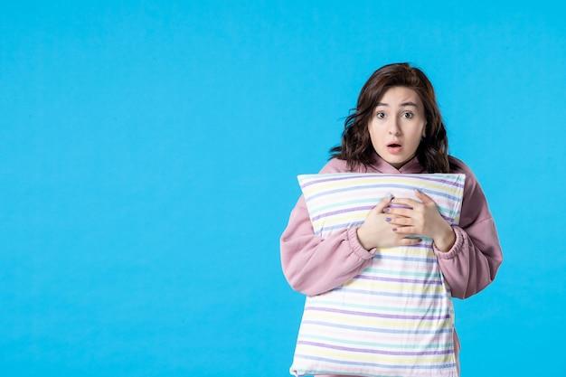 Вид спереди молодая женщина в розовой пижаме с подушкой на синем