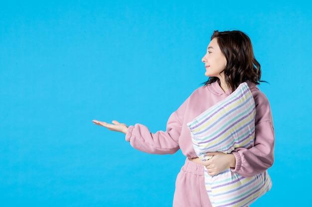 Вид спереди молодая женщина в розовой пижаме с подушкой на синем цвете, вечеринка, постельный режим, сон, бессонница