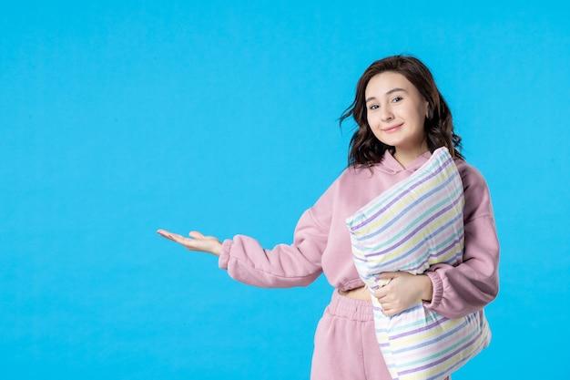 ブルーナイトカラーのパーティーベッドの休息の夢の女性の睡眠の不眠症の枕とピンクのパジャマの正面図若い女性
