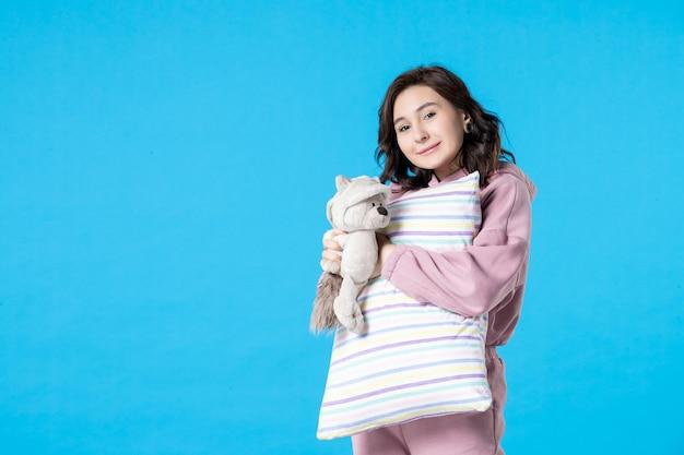 밝은 파란색에 장난감 곰과 베개가 있는 분홍색 잠옷을 입은 전면 보기 젊은 여성