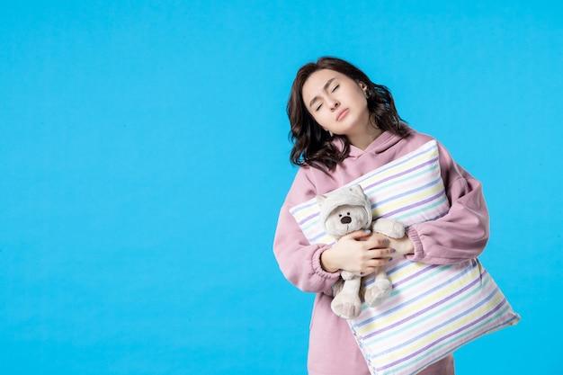 푸른 밤에 장난감 곰과 베개가 있는 분홍색 잠옷을 입은 전면 보기 젊은 여성