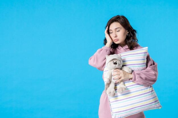 青のおもちゃのクマと枕とピンクのパジャマの正面図若い女性