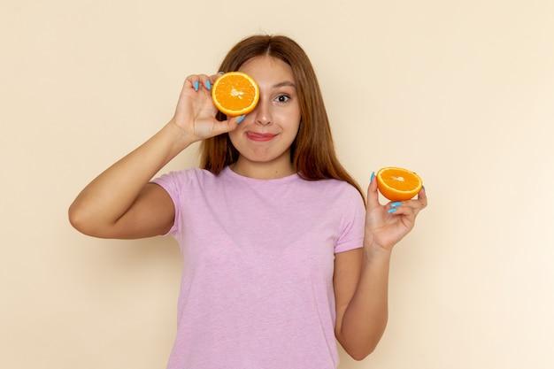 ピンクのtシャツとブルージーンズのオレンジ色の部分を保持している正面の若い女性