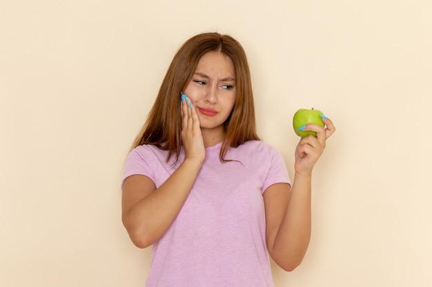 ピンクのtシャツとブルージーンズの正面の若い女性が灰色にリンゴをかむ彼女の歯を傷つける