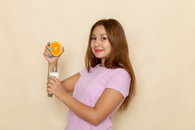 ピンクのtシャツとグレーのオレンジと牛乳を混合するブルージーンズの正面の若い女性
