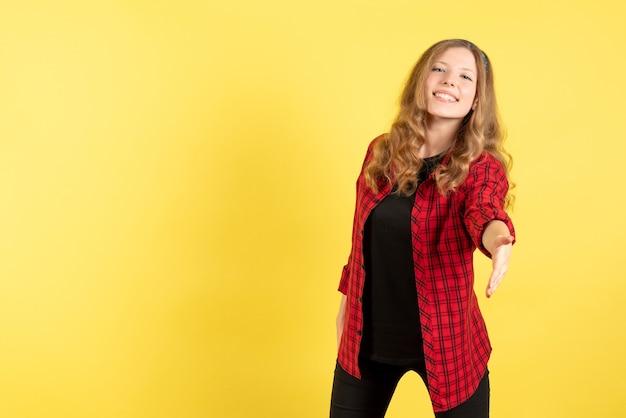 黄色の背景の女性の人間の感情モデルファッションの女の子に挨拶する赤い市松模様のシャツの正面図