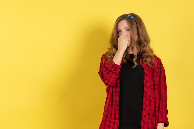 正面図黄色の背景モデルの女の子の人間の女性の色に立ってポーズをとって赤い市松模様のシャツの若い女性