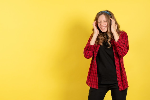 正面図黄色の机の上に立ってポーズをとっている赤い市松模様のシャツを着た若い女性モデルの女の子女性の色の感情人間