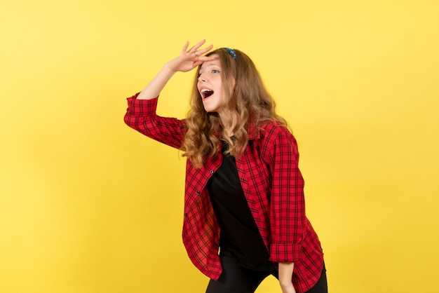 黄色の背景の女性人間の感情モデルファッションの女の子の距離を見て赤い市松模様のシャツの正面図若い女性