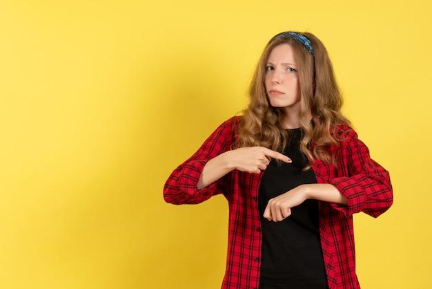 黄色の背景モデルの女の子の人間の女性の色に彼女の手首を指している赤い市松模様のシャツの正面図若い女性