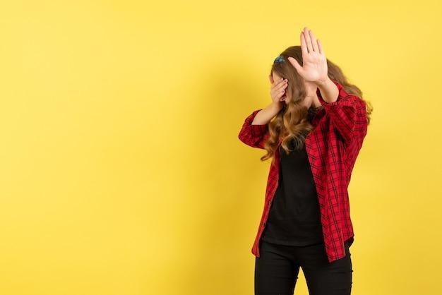 黄色の背景モデルの女の子の女性の色の感情の人間のポーズと彼女の顔を覆う赤い市松模様のシャツの正面図若い女性