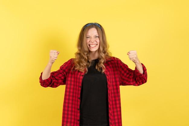 黄色の背景の女性の人間の感情モデルファッションの女の子にポーズをとって喜んで赤い市松模様のシャツの正面図
