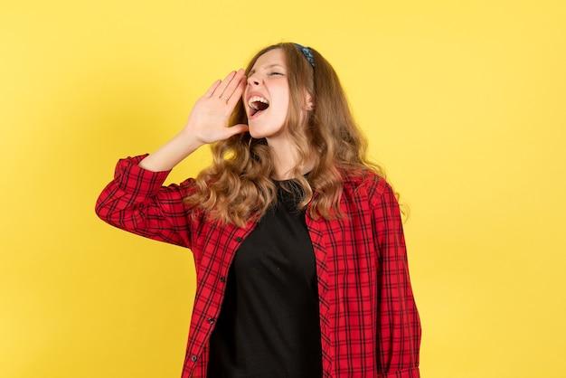 正面図黄色の背景の女の子の感情の色人間モデルの女性にポーズをとって叫んで赤い市松模様のシャツの若い女性
