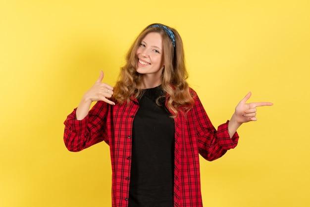 正面図黄色の背景の女の子の感情色人間モデルの女性にポーズと笑顔の赤い市松模様のシャツの若い女性