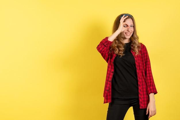 빨간색 체크 무늬 셔츠 포즈와 노란색 배경에 웃는 전면보기 젊은 여성 인간의 소녀 감정 컬러 모델 여자