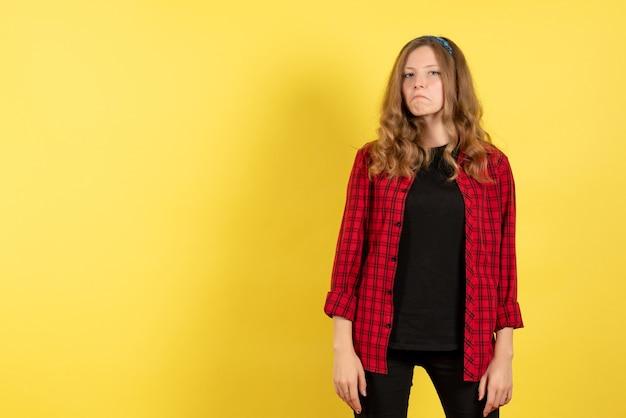 黄色の背景モデルの女の子の女性の感情人間の色でポーズをとって赤い市松模様のシャツの正面図若い女性