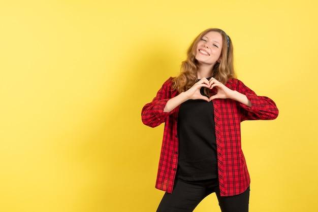 黄色の背景に笑顔でポーズをとって赤い市松模様のシャツの正面図若い女性人間の色モデル女性の感情