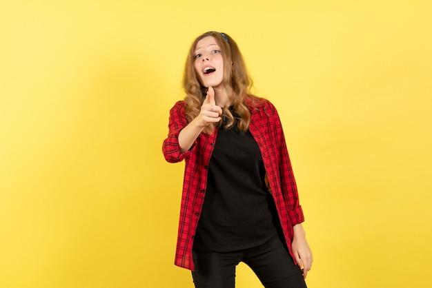 노란색 배경 인간의 색상 감정 모델 패션에 그녀의 감정을 보여주는 빨간색 체크 무늬 셔츠에 전면보기 젊은 여성