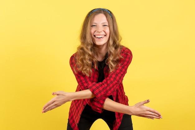 빨간색 체크 무늬 셔츠 미소와 노란색 배경에 누군가 인사에 전면보기 젊은 여성 여자 인간의 감정 모델 패션 소녀