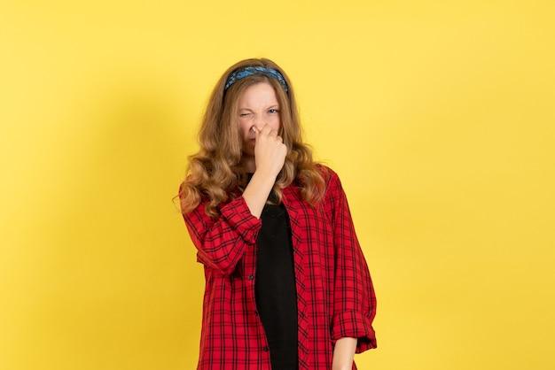 正面図黄色の机の色の女性モデル人間の女の子に立ってポーズをとって赤い市松模様のシャツの若い女性