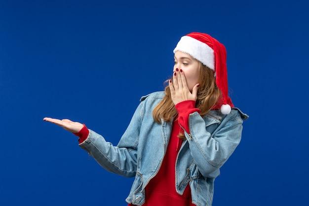 Вид спереди молодая женщина в красной рождественской шапке на синем фоне цвета рождественских эмоций