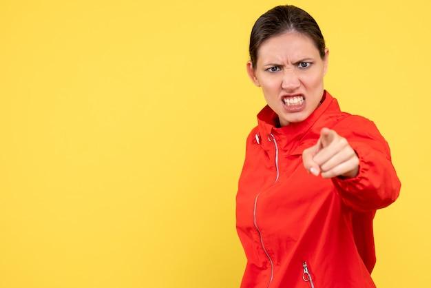 黄色の背景に怒っている赤いコートの若い女性の正面図