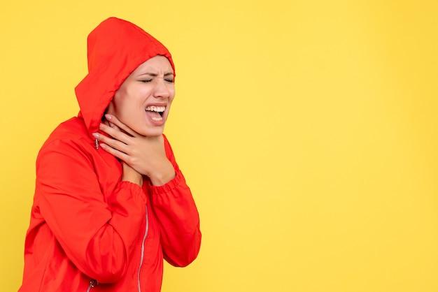 노란색 배경에 목의 통증을 가진 빨간 코트에 전면보기 젊은 여성