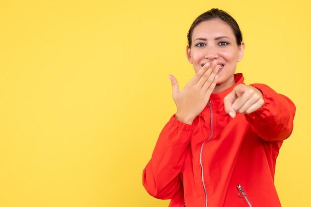 노란색 바탕에 웃 고 빨간 코트에 전면보기 젊은 여성