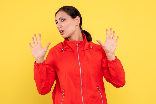 밝은 노란색 배경에 빨간 코트에 전면보기 젊은 여성