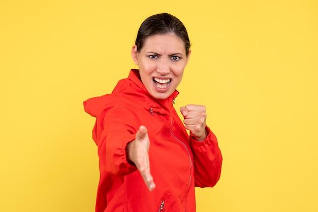 노란색 바탕에 빨간 코트에 전면보기 젊은 여성