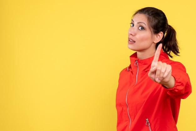 Вид спереди молодая женщина в красном пальто на желтом фоне